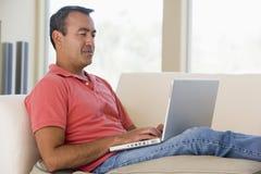 Mens in woonkamer die laptop met behulp van royalty-vrije stock fotografie