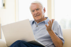 Mens in woonkamer met laptop Royalty-vrije Stock Fotografie