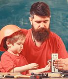 Mens work concept. Boy, child busy in protective helmet makes by hand, repairing, does crafts with dad. Father with royalty free stock photos