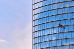 Mens workers in red and dark work clothes cleaning the exterior windows of a business skyscraper - industrial alpinism