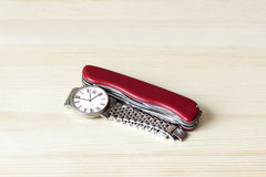 Mens wrist watch and pocket knife on a wooden countertop Royalty Free Stock Photo