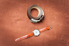 Mens wristwatches and belt. On brown background Royalty Free Stock Photos