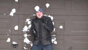 Mens zich dichtbij muur bevinden en iemand die sneeuwballen werpen bij hem Sneeuw het Vallen stock videobeelden