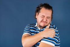 Mens zijn pijnlijke schouder houden die proberend om pijn te verlichten Gezondheidsproblemen stock afbeelding