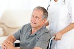 Mens in zijn rolstoel Stock Afbeeldingen
