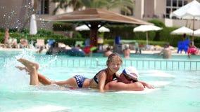 Mens in zonglazen, vader en dochter, jong geitjemeisje, die samen in het poolwater spelen, die pret hebben Het gelukkige familie  stock footage