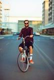 Mens in zonnebril die een fiets berijden op stadsstraat Stock Foto