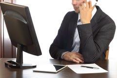 Mens in zwart die kostuum bij bureauvraag op telefoon op witte achtergrond wordt geïsoleerd Stock Fotografie