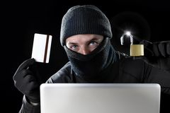 Mens in zwarte holdingscreditcard en slot die computerlaptop voor criminele activiteit het binnendringen in een beveiligd compute Royalty-vrije Stock Afbeeldingen