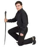 Mens in zwarte met het Japanse zwaard in een hand Stock Foto's