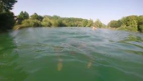 Mens zwemmen onderwater in rivier stock videobeelden