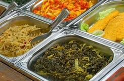 Mensa di self service con la cotoletta impanata della carne e gli spinaci cucinati immagini stock