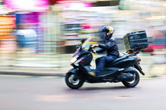 Mensageiro do 'trotinette' na estrada no borrão de movimento foto de stock royalty free