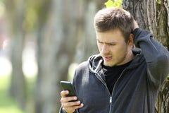 Mensagem adolescente confusa da leitura em um telefone esperto imagem de stock royalty free