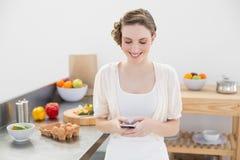 Mensagem alegre da jovem mulher com seu smartphone que está na cozinha Foto de Stock