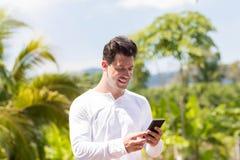 Mensagem considerável do homem com o telefone esperto da pilha sobre Forest And Blue Sky Young tropical Guy Chatting Online fotografia de stock