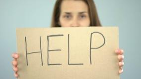 Mensagem da ajuda no cartaz nas mãos infelizes da mulher, vítima do crime que implora o apoio vídeos de arquivo