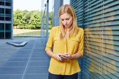 Mensagem da leitura do estudante fêmea no smartphone fotos de stock