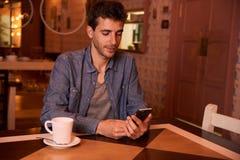 Mensagem da leitura do homem novo no restaurante Fotografia de Stock Royalty Free