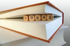 Mensagem das ideias escrita em blocos de madeira entre páginas do livro Imagens de Stock Royalty Free
