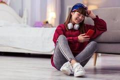 Mensagem de cabelos compridos de encantamento da leitura da menina no telefone fotos de stock