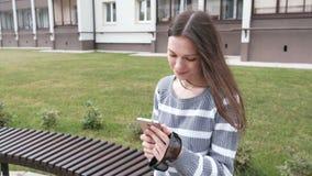 Mensagem de conversa e de datilografia da mulher moreno atrativa no telefone celular e assento de sorriso no banco video estoque