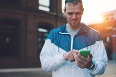 Mensagem de datilografia considerável em seu telefone celular, por do sol do homem novo na rua foto de stock