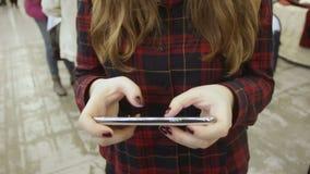 Mensagem de datilografia da menina em seu dispositivo, usando a aplicação móvel no shopping video estoque