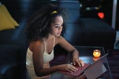 Mensagem de datilografia da mulher nova de Latina no portátil na noite imagens de stock