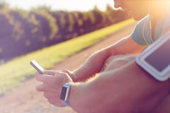 Mensagem de datilografia do atleta com smartphone ao sentar-se e ao descansar no parque fotografia de stock
