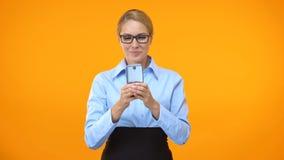 Mensagem de datilografia do gerente fêmea feliz no smartphone, redes sociais, app do negócio video estoque
