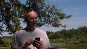 Mensagem de datilografia do homem considerável no telefone celular dentro em árvores e em paisagem da lagoa filme