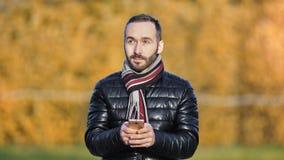 Mensagem de datilografia do homem europeu da forma usando o smartphone na noite do outono no tempo frio filme