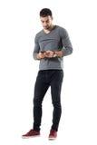 Mensagem de datilografia do homem na moda novo à moda no telefone celular fotografia de stock royalty free