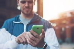 Mensagem de datilografia em seu telefone celular, por do sol do homem considerável na rua imagem de stock