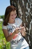 Mensagem de sorriso feliz nova da leitura da mulher no móbil fora Imagens de Stock