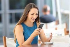 Mensagem de telefone feliz da leitura da mulher em uma barra fotos de stock