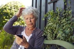Mensagem de texto da leitura da mulher mais idosa em seu telemóvel Fotos de Stock