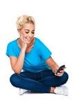 Mensagem de texto da leitura da mulher nova no telefone de pilha Imagens de Stock Royalty Free