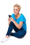 Mensagem de texto da leitura da mulher nova no telefone de pilha Fotografia de Stock