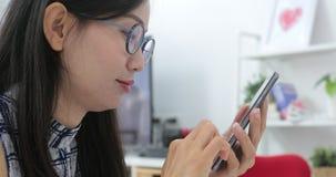 Mensagem de texto de datilografia da mulher asiática no telefone esperto em casa filme