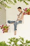 Mensagem de texto feliz da leitura da mulher que senta-se na parede do jardim Imagem de Stock Royalty Free
