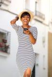 Mensagem de texto nova de sorriso da leitura da mulher negra no telefone celular Fotos de Stock Royalty Free