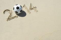 Mensagem 2014 desportiva na areia com a bola de futebol do futebol Fotografia de Stock Royalty Free