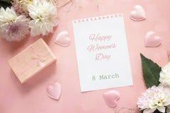 Mensagem do cumprimento do dia do ` s das mulheres com dálias e caixa de presente no rosa Fotografia de Stock Royalty Free