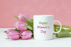 Mensagem do cumprimento do dia do ` s das mulheres na caneca de café branco com tulipa cor-de-rosa Fotografia de Stock