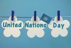 Mensagem do cumprimento do dia de United Nations escrita através das etiquetas brancas com a bandeira que pendura dos Pegs azuis e Imagens de Stock