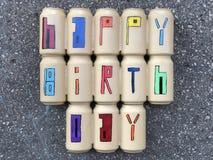 Mensagem do feliz aniversario com as latas de cerveja coloridas sobre a estrada rodoviária asfaltada Foto de Stock