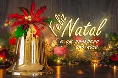 Mensagem do Feliz Natal no português Bell, flowes e luzes no fundo Imagens de Stock Royalty Free