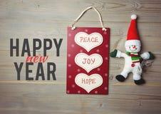 Mensagem do Natal feliz no fundo de madeira com saco de compras e boneco de neve Fotografia de Stock Royalty Free